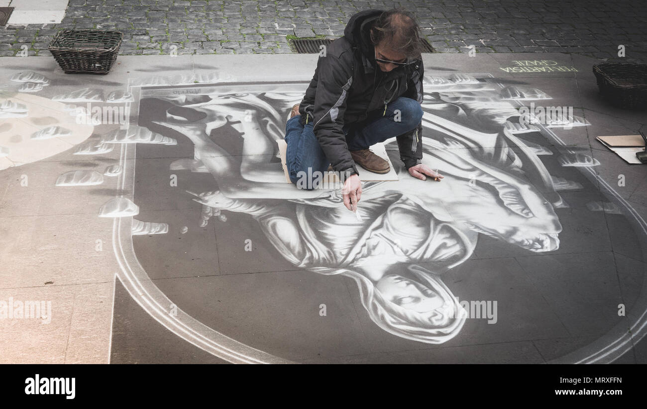 Street art - man is painting a reproduction of Italian Renaissance artwork : Michelangelo's Pity in black and white on the pavement in Loreto square.  - Stock Image