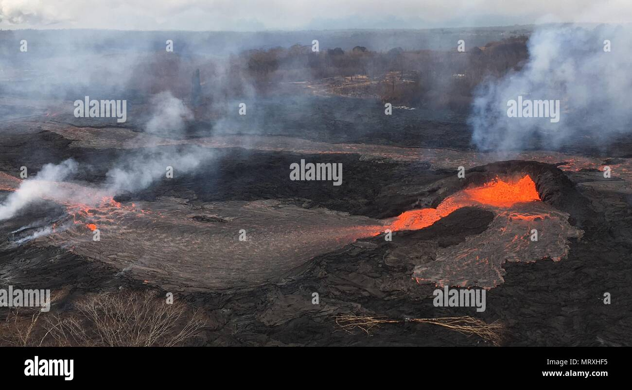 Lava and poisonous sulfur dioxide plumes rise as molten magma spews from a spatter cone at fissure 6 from the eruption of the Kilauea volcano May 25, 2018 in Pahoa, Hawaii.Stock Photo