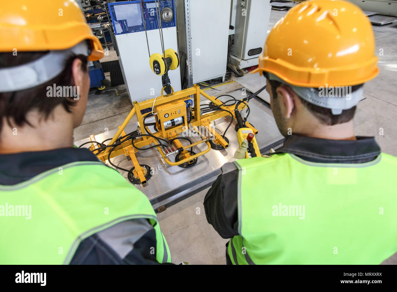 Workers near metal sheet lifting device at factory - Stock Image