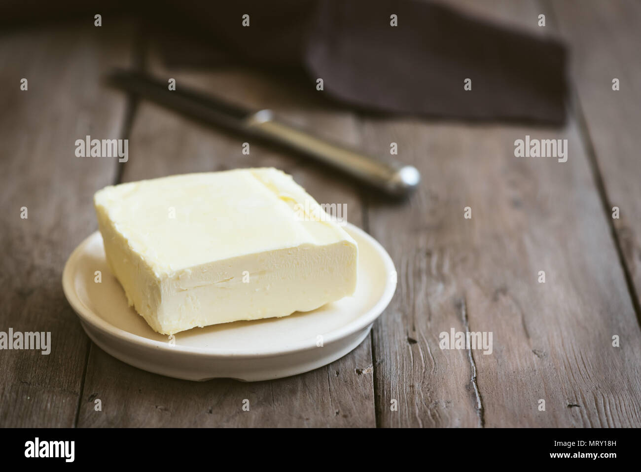Butter on dark wooden background, copy space. Farm dairy product - butter. - Stock Image