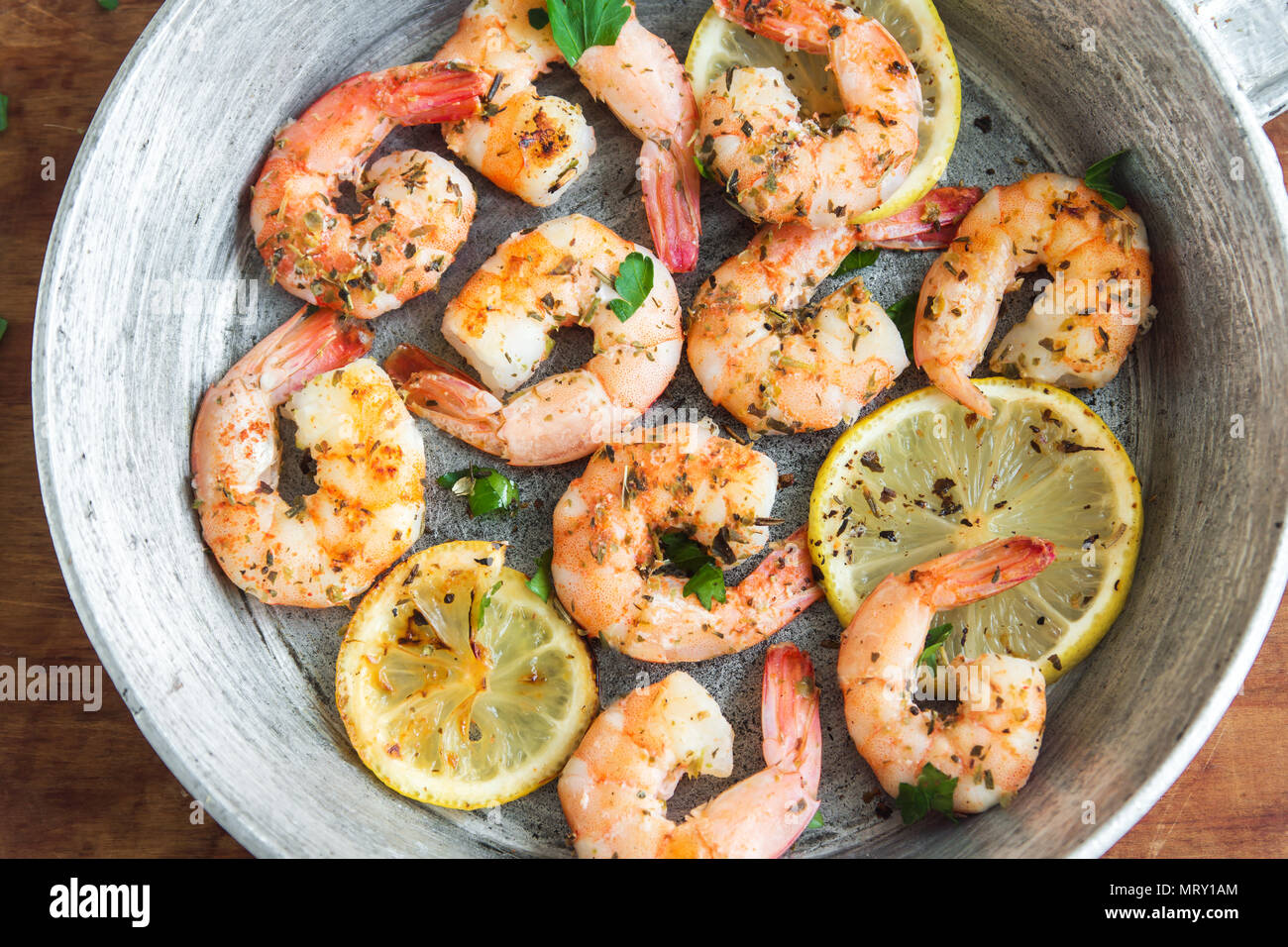 Roasted shrimps with lemon, garlic and herbs. Seafood, shelfish. Shrimps Prawns grilled with spices, garlic and lemon on black stone background, copy  - Stock Image