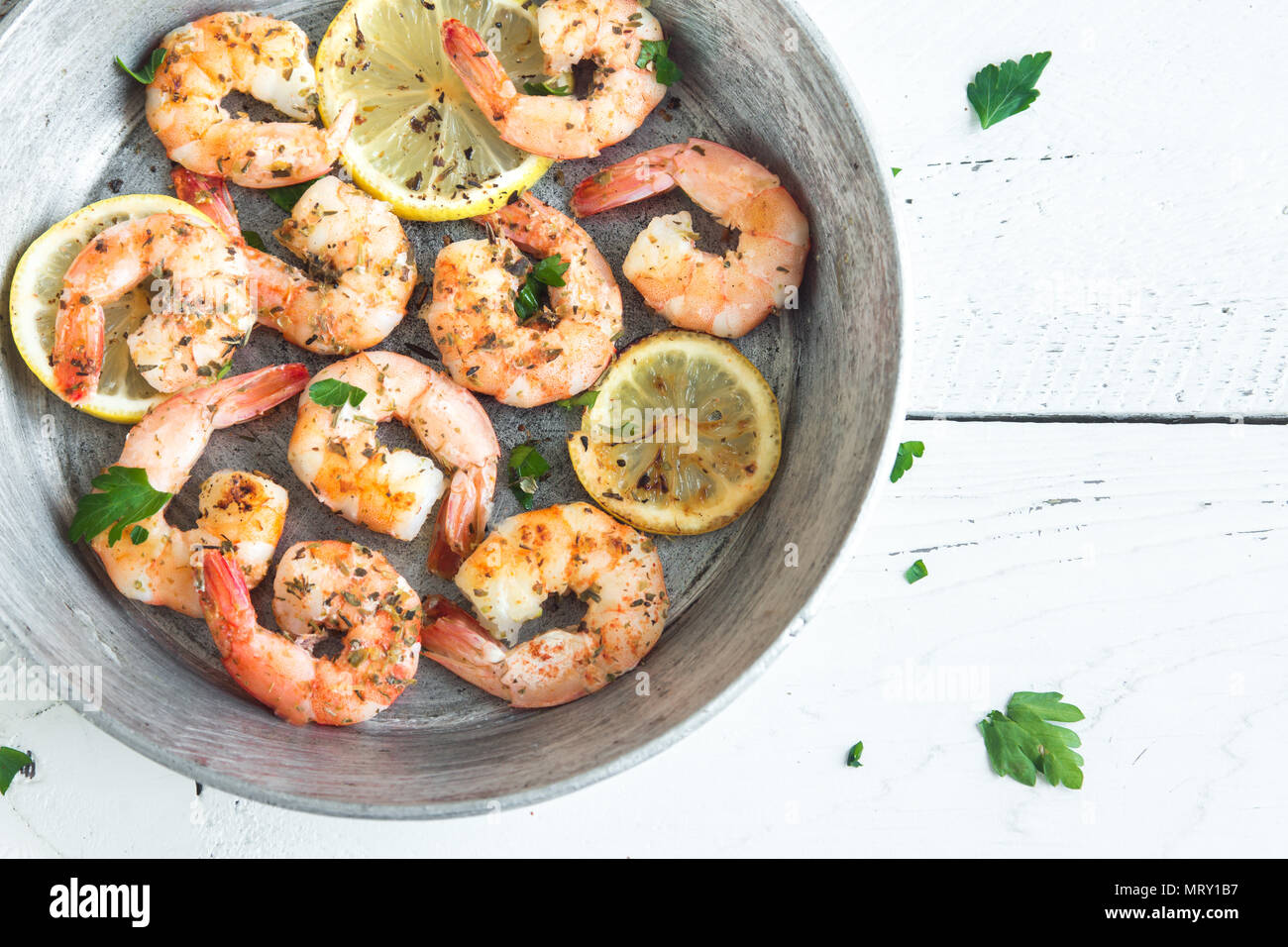 Roasted shrimps with lemon, garlic and herbs. Seafood, shelfish. Shrimps Prawns grilled with spices, garlic and lemon on white background, copy space. - Stock Image