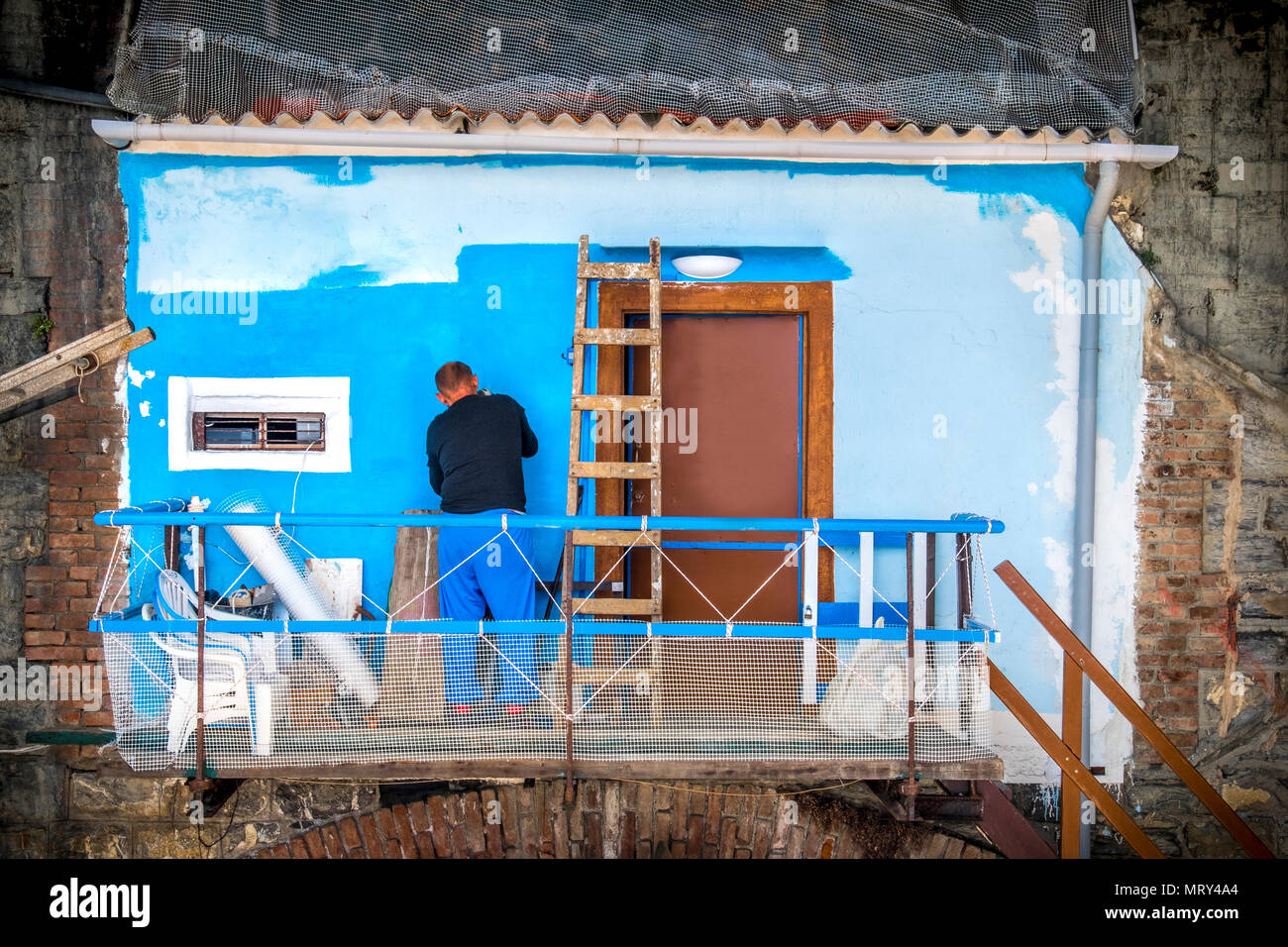 painter on scaffolding restoring old wall with blue paint - Stock Image