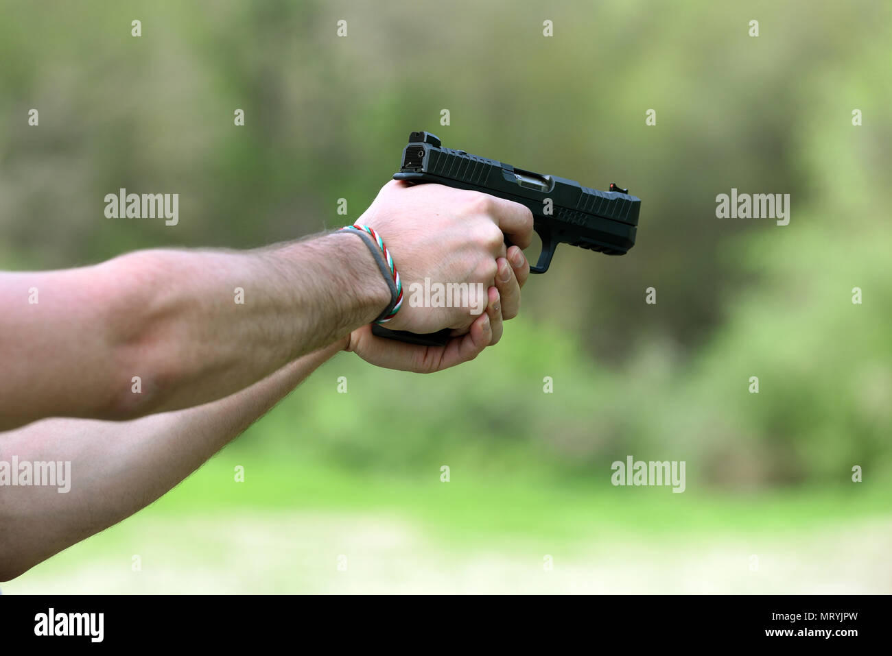 Man bare hands in close-up shooting with black handgun standing outdoors, viewed from the side - Stock Image