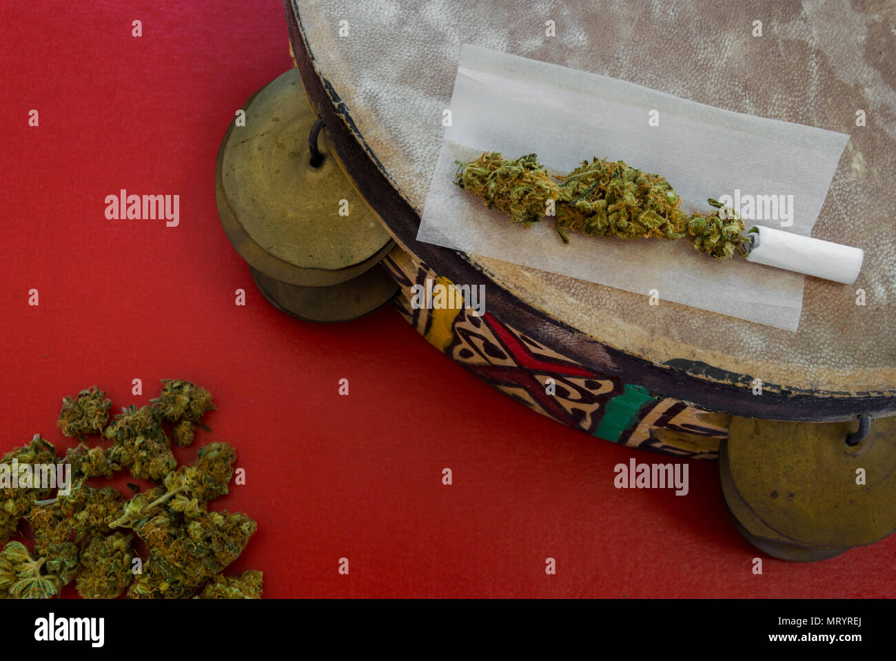 Colorful handmade tambourine with ethnic motif and a joint on it. Red background with a pile of marijuana buds. Concept of art, drugs and inspiration. - Stock Image