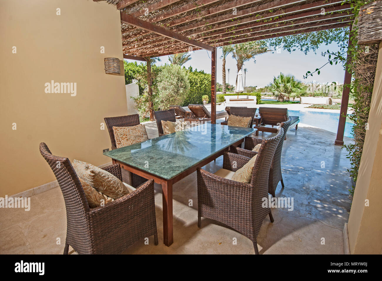 Luxury villa show home in tropical summer holiday resort with swimming pool and outdoor dining table area Stock Photo