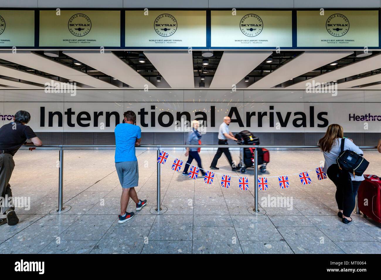 People Waiting At The Terminal 5 International Arrivals Hall, Heathrow Airport, London, UK - Stock Image
