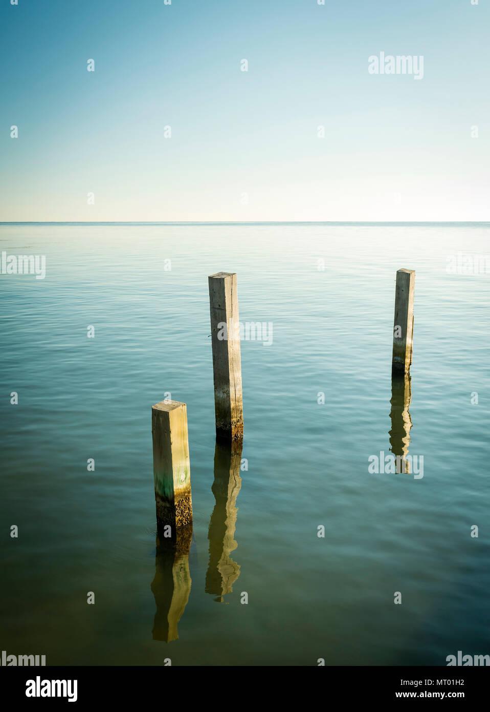 Ocean landscape with minimalism design of wooden pylons - Stock Image