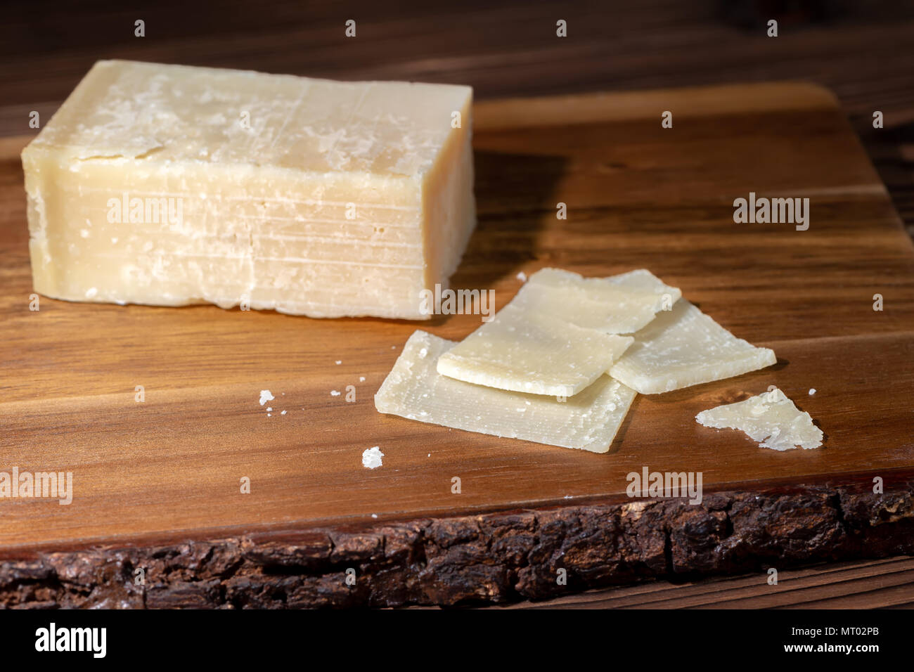 portion and slaced of fresh parmesan cheese on wooden table - Stock Image