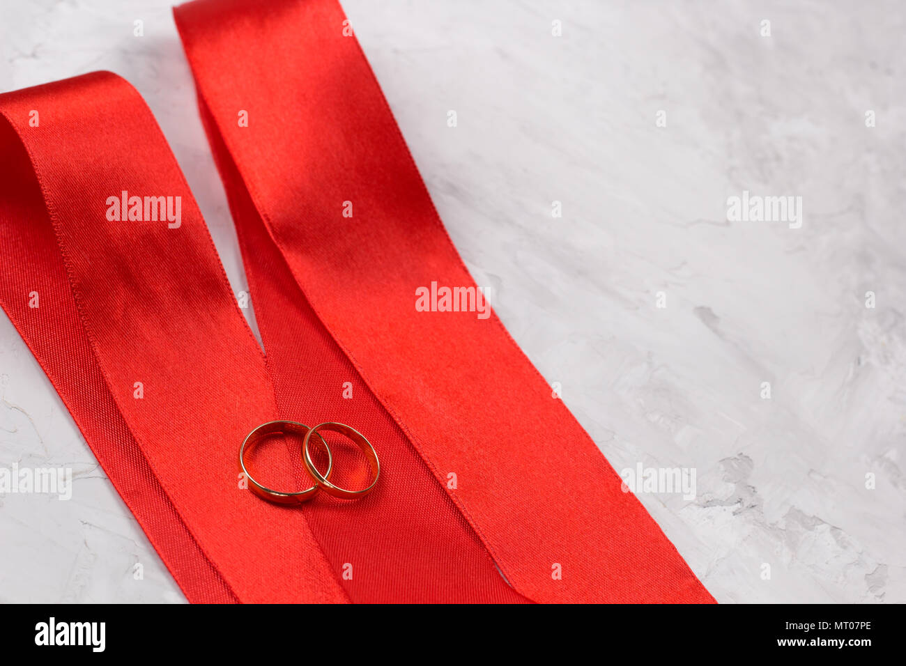 two golden rings and red satin ribbon wedding decor or wedding ...
