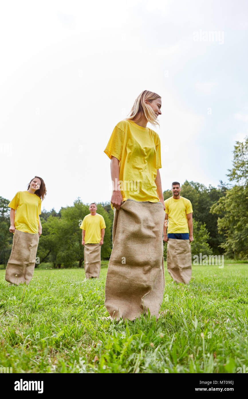 Sporting team makes sack races on a meadow at a sports festival - Stock Image