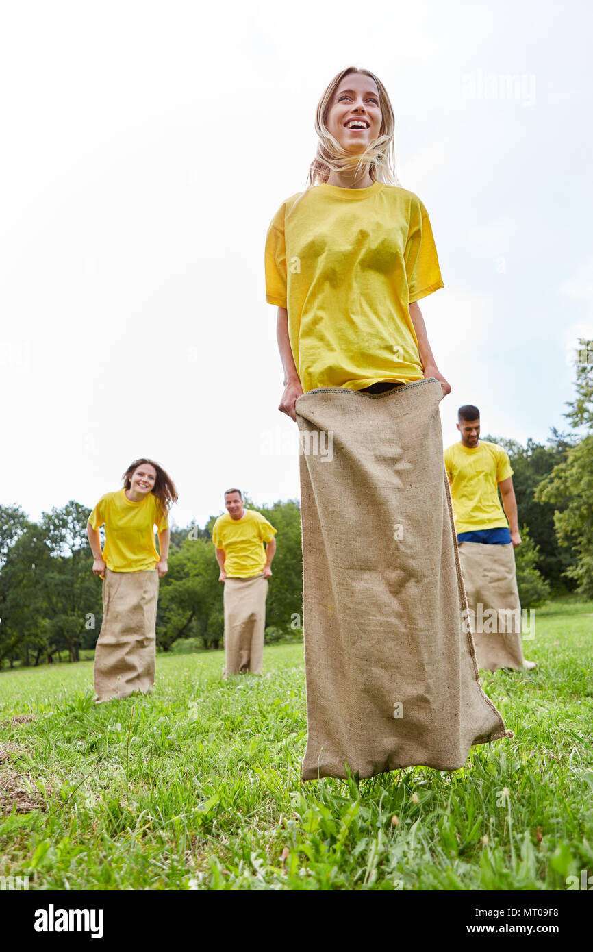 Young sporty woman with her team makes sack races at a competition - Stock Image