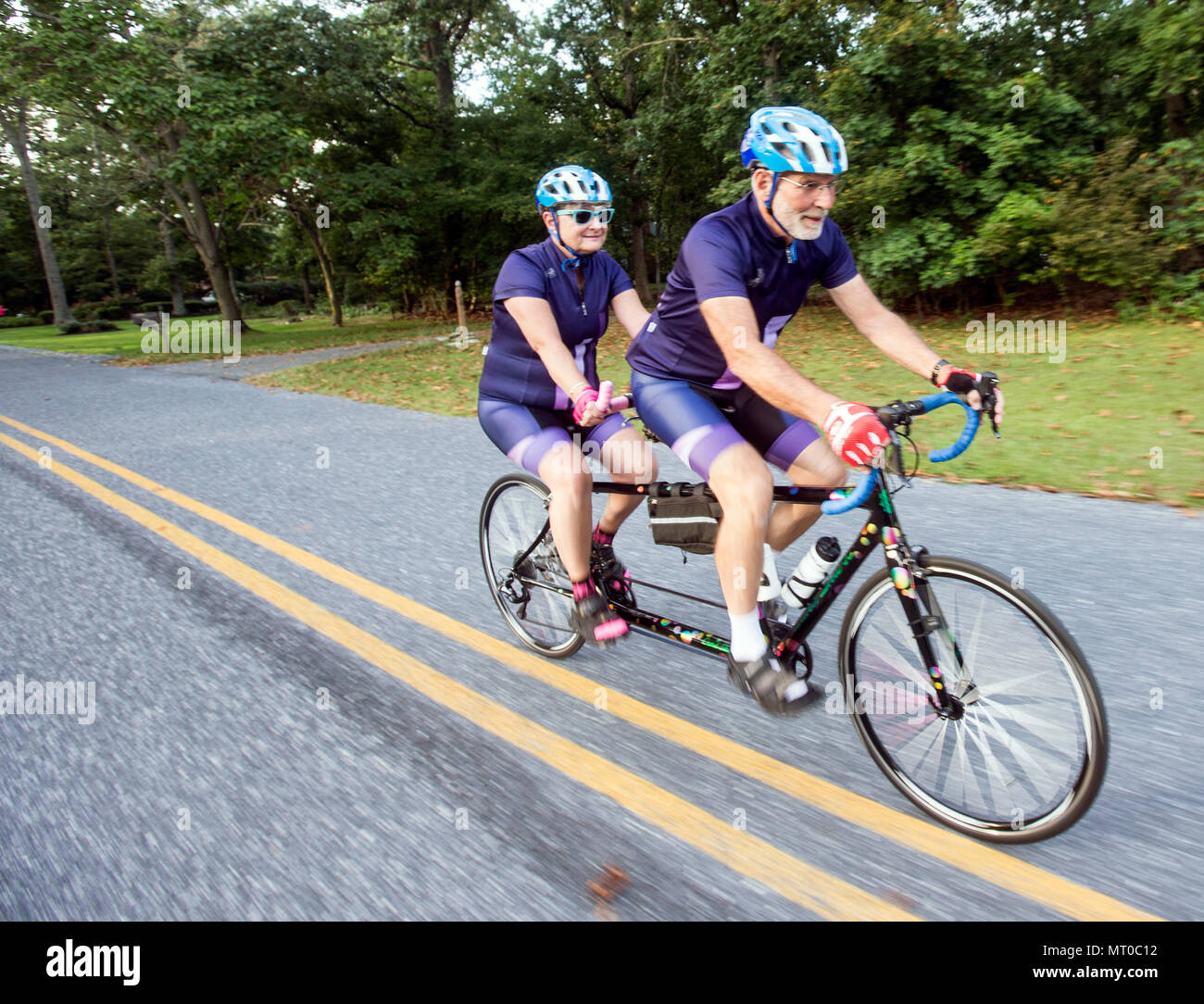 Married couple riding a tandem bicycle - Stock Image