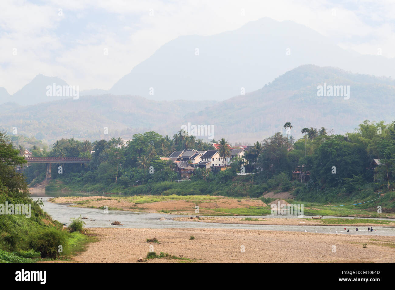 View of Nam Khan River at low tide and lush riverbank in Luang Prabang, Laos, on a sunny day. - Stock Image