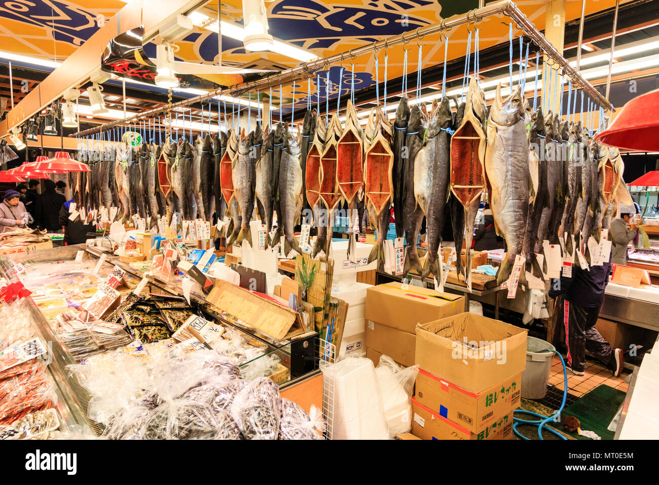 Indoor Omicho Ichiba, Omicho fresh food Market in Kanazawa, Japan. Large fish market store, with gutted fish hanging, sticks holding stomachs open. - Stock Image