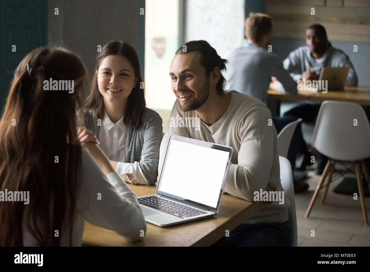 Smiling millennial couple meeting realtor or insurance broker in - Stock Image