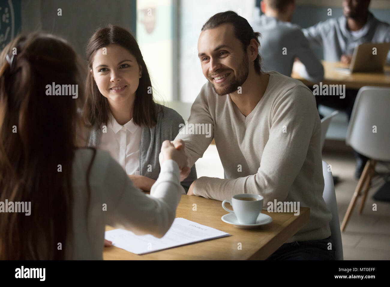 Happy millennial couple handshaking trusted broker after signing - Stock Image