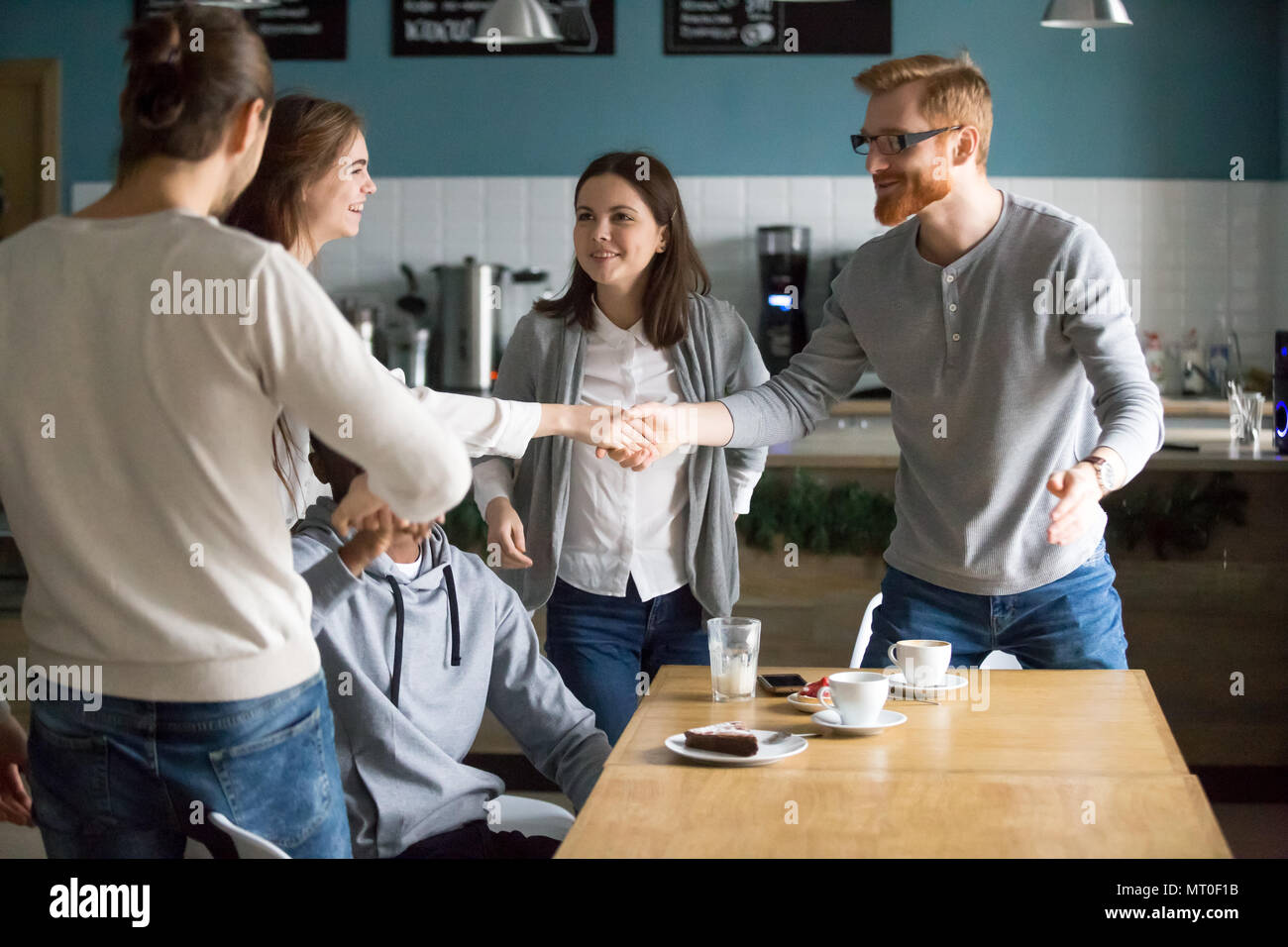 Millennial guy and girl handshaking getting acquainted coming at - Stock Image
