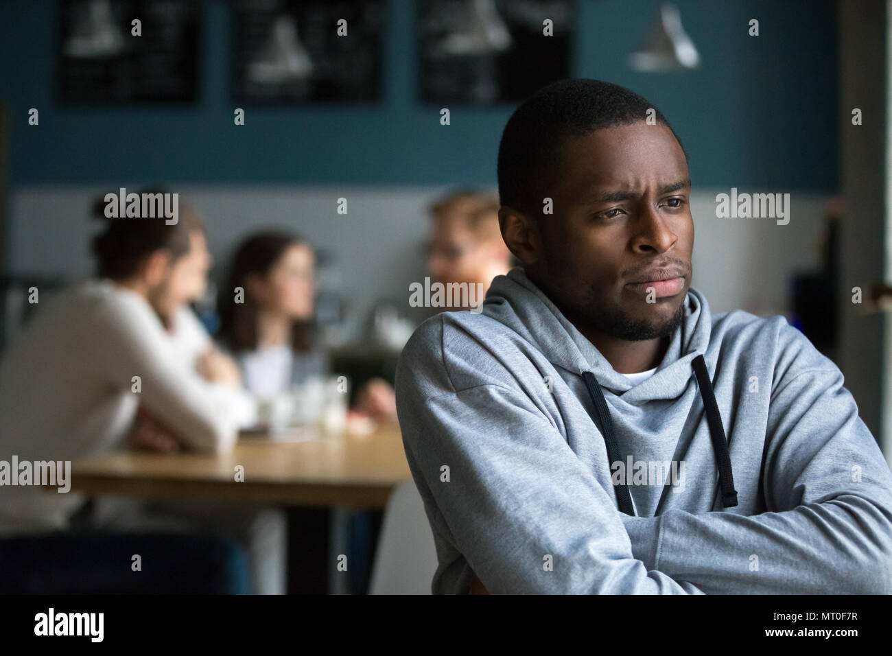 Frustrated african man suffers from racial discrimination alone  - Stock Image