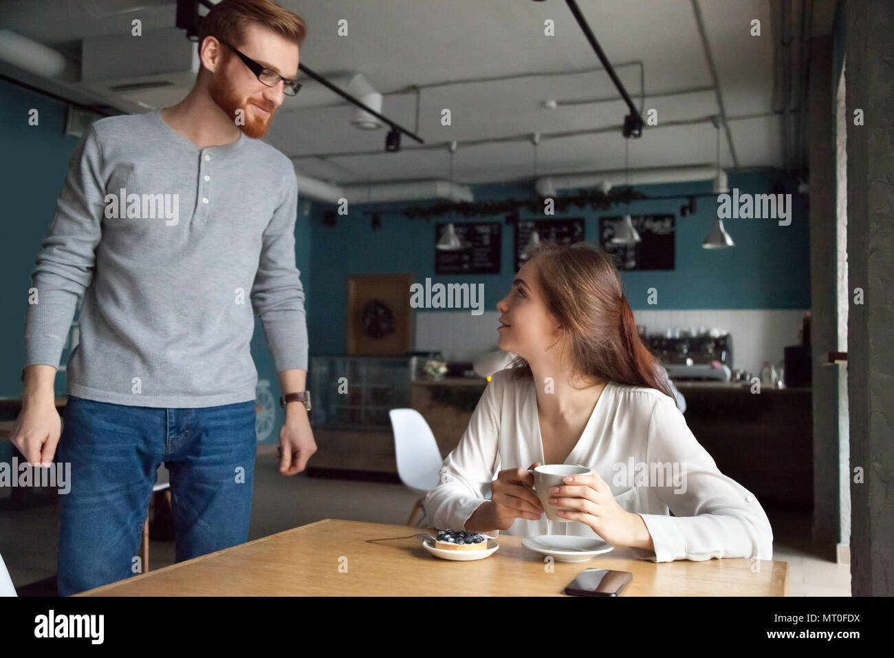 Man coming to cafe table getting acquainted with beautiful woman - Stock Image