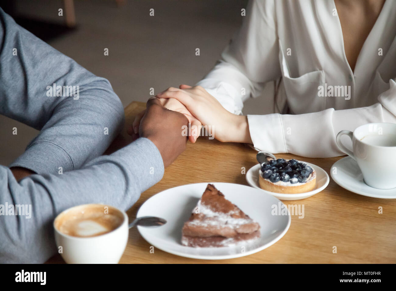 Interracial couple holding hands sitting at cafe table, closeup  - Stock Image