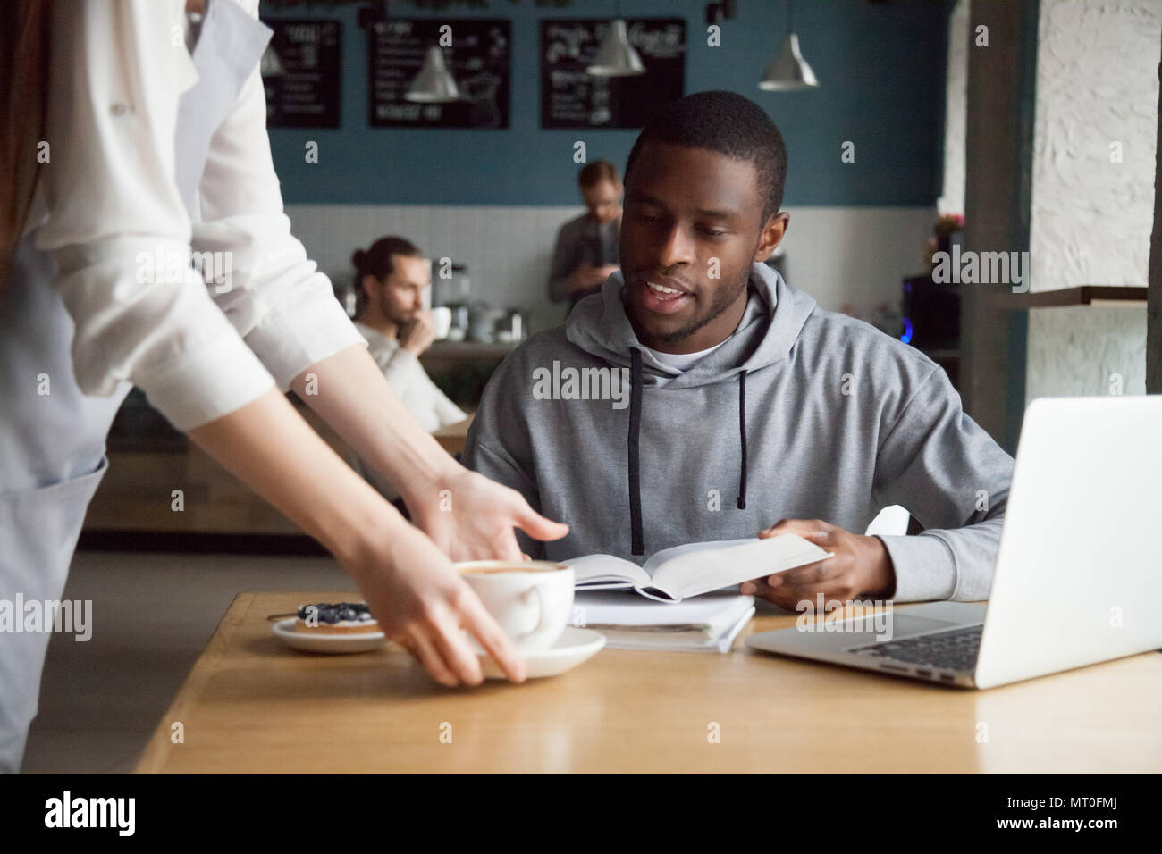 Waitress serving coffee to smiling african-american man customer - Stock Image