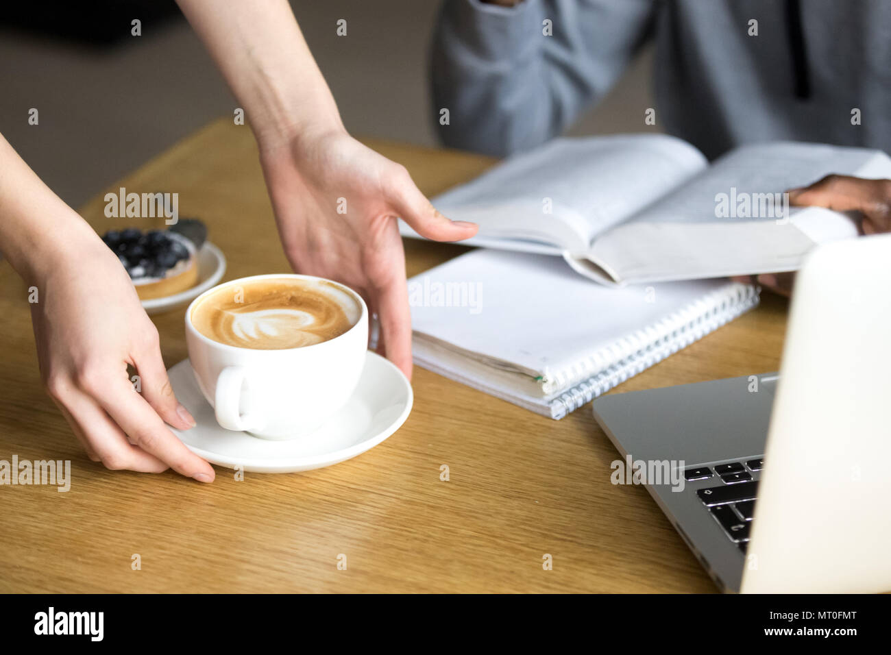 Waitress serving cappuccino to cafeteria visitor at cafe table,  - Stock Image