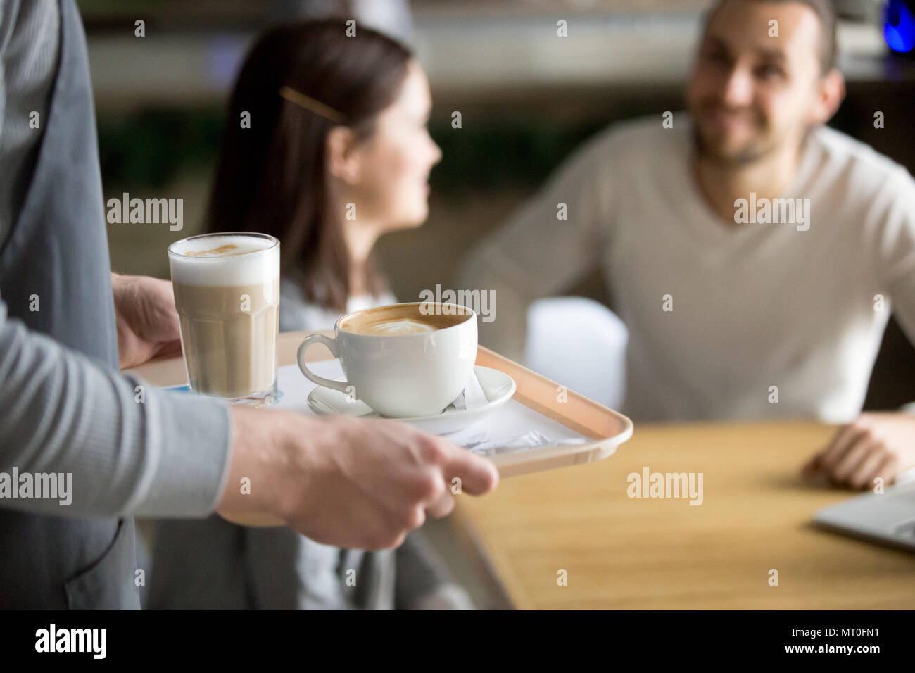 Waitress serving cappuccino and latte to couple in cafe, closeup - Stock Image