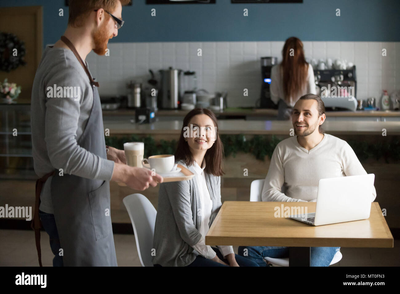 Waiter carrying coffee to smiling couple waiting at cafe table - Stock Image