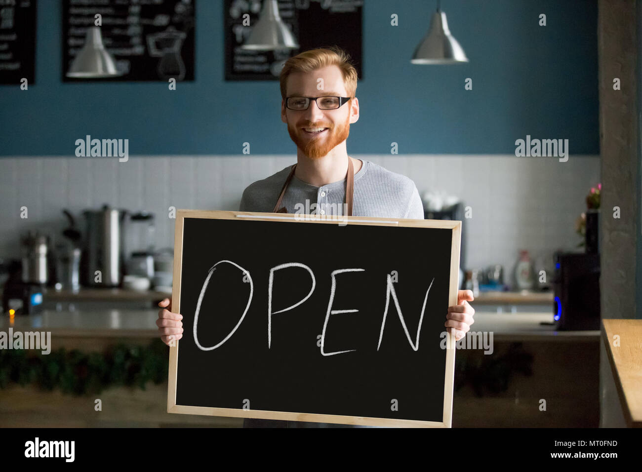 Redhead smiling man holding open sign inviting to new cafe Stock Photo