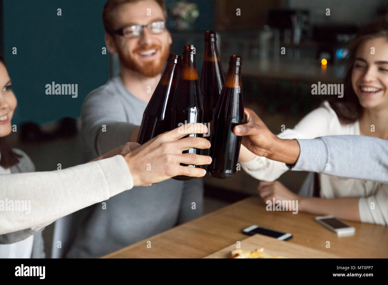 Diverse friends clinking craft beer bottles in pub, cheers conce - Stock Image