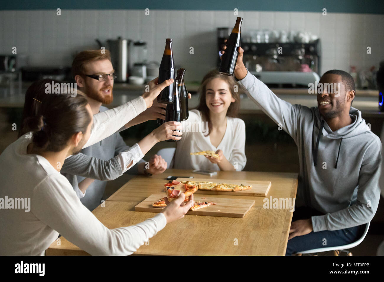 Diverse millennial people hanging out together drinking beer eat - Stock Image