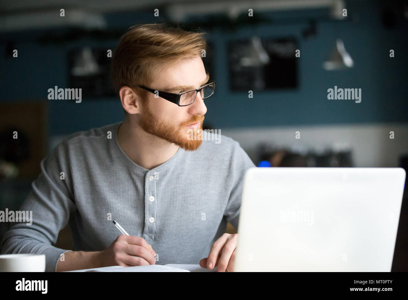 Thoughtful man thinking of new idea writing notes in cafe - Stock Image