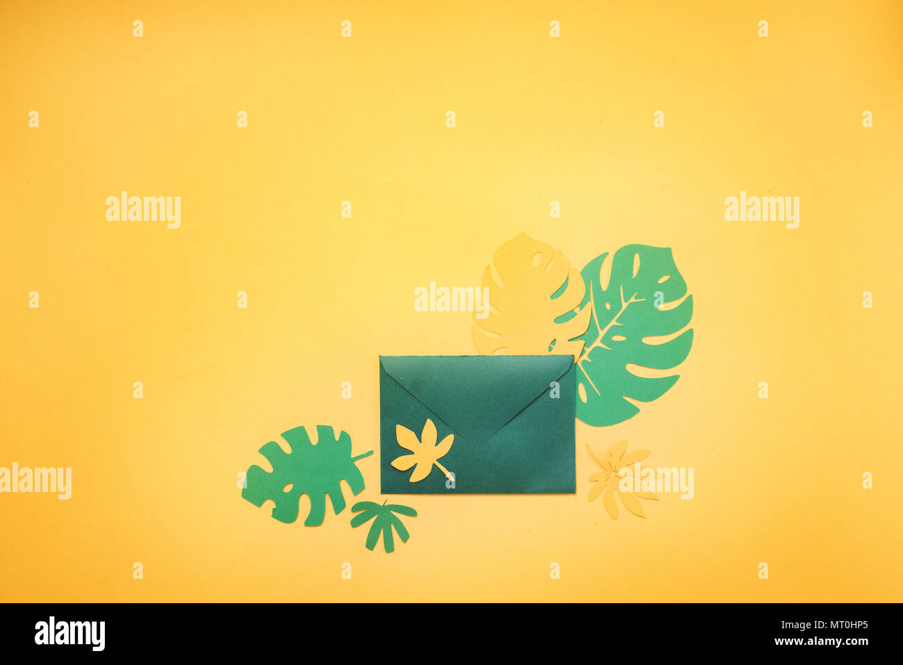 green invitation envelope with tropical leaves on a bright yellow