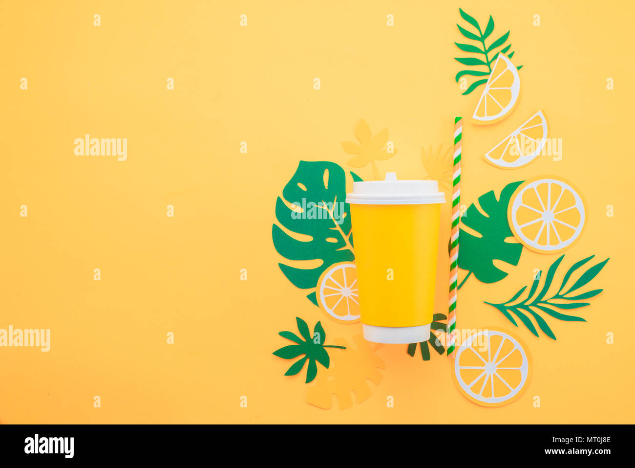 Disposable paper cup on a yellow background with tropical leaves and orange slices on a bright yellow background. Colorful summer drink concept with p - Stock Image