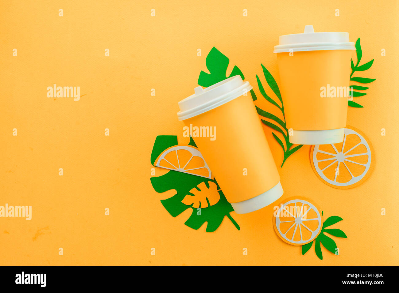 Disposable paper cup on a yellow background with tropical leaves and orange slices on a bright yellow background. Colorful summer drink concept with paper cut outs. Stock Photo