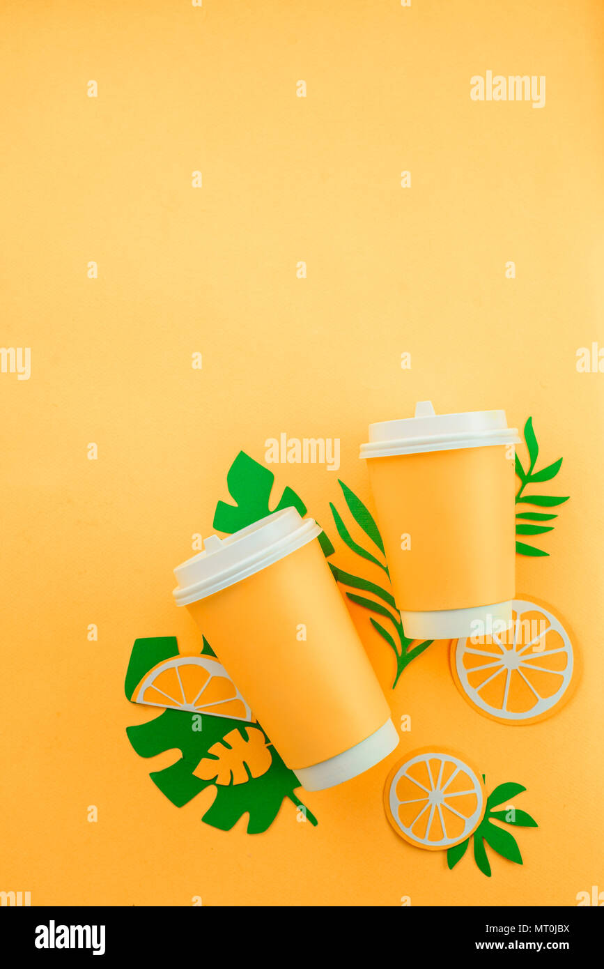 Colorful summer drink concept. Disposable paper cup on a yellow background with tropical leaves and orange slices on a bright yellow background. - Stock Image