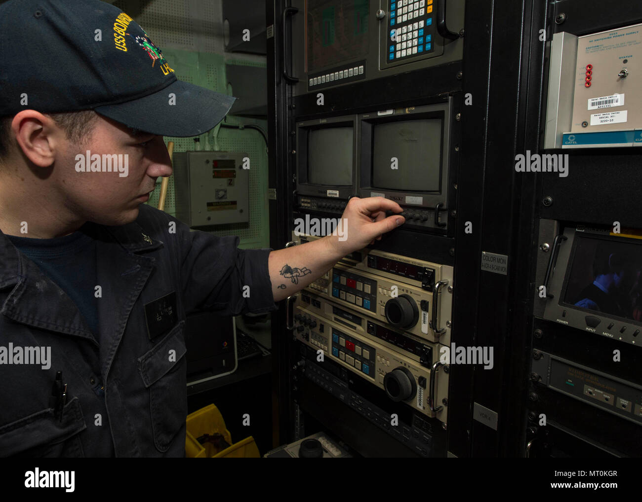 170715-N-RD713-034 CORAL SEA (July 15, 2017) Interior Communications Electrician 3rd Class Jacob Flynn, from Cincinnati, tests a television monitor in the Shipboard Information Training and Entertainment Television (SITE TV) center aboard the amphibious assault ship USS Bonhomme Richard (LHD 6). Bonhomme Richard, part of a combined U.S.-Australia-New Zealand expeditionary strike group, is undergoing a series of scenarios that will increase naval proficiencies in operating against blue-water adversarial threats and in its primary mission of launching Marine forces ashore in the littorals. Talis - Stock Image
