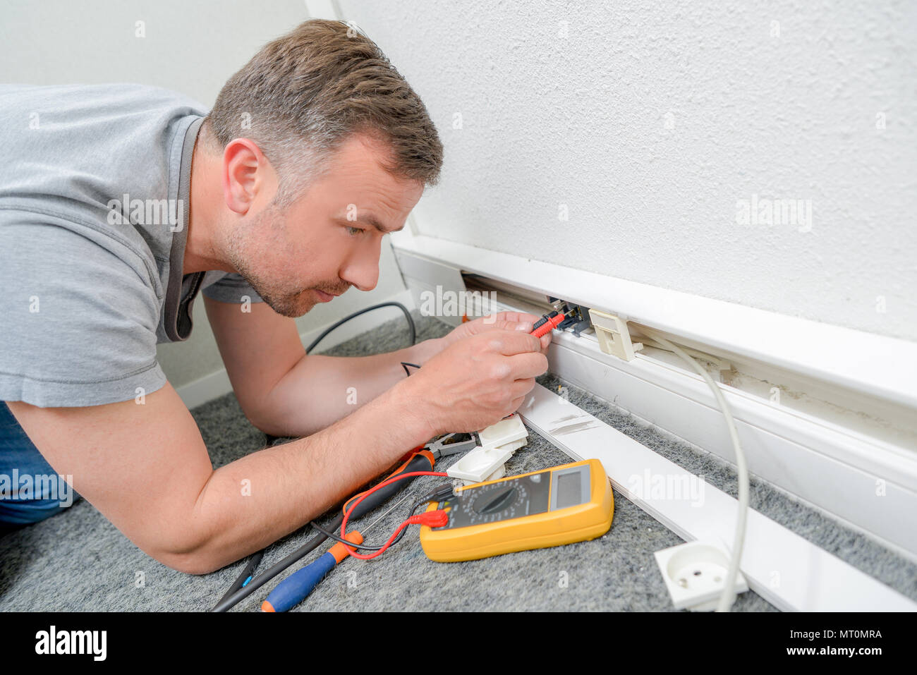 Astounding Man Testing Current Behind Skirting Board Stock Photo 186871758 Alamy Wiring Digital Resources Aeocykbiperorg