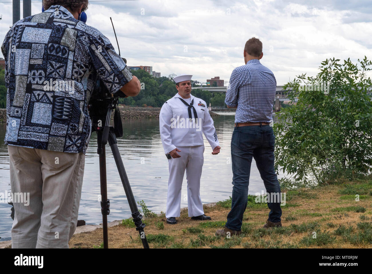 170718-N-CU914-024 MINNEAPOLIS (July 18, 2017) –Navy Diver 1st Class Brian Bennett is interviewed on the bank of the Mississippi River by NBC KARE 11 reporter Kent Erdahl, near the site of the collapse of the I-35W bridge ten years ago, where Bennett was called to assist local, state and federal authorities in finding missing victims, while he was attached to Mobile Diving and Salvage Unit (MDSU) 2. Bennett returned to the area to take part in a wreath laying ceremony during Minneapolis/St. Paul Navy Week, which recognized those who responded to the tragedy and remembered those lost. Navy Week - Stock Image