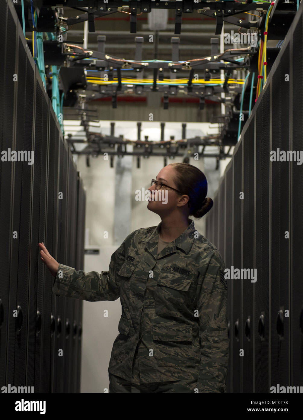 U.S. Air Force Staff Sgt. Shelby Carter, a network control center technician with the 379th Expeditionary Communication Squadron, checks the network servers for signs of problems at Al Udeid Air Base, Qatar, July 14, 2017. Carter is part of a team of Airmen that are responsible for installing and supporting all network servers by ensures they are operational and secure from outside intrusion. (U.S. Air Force photo by Tech. Sgt. Amy M. Lovgren) - Stock Image
