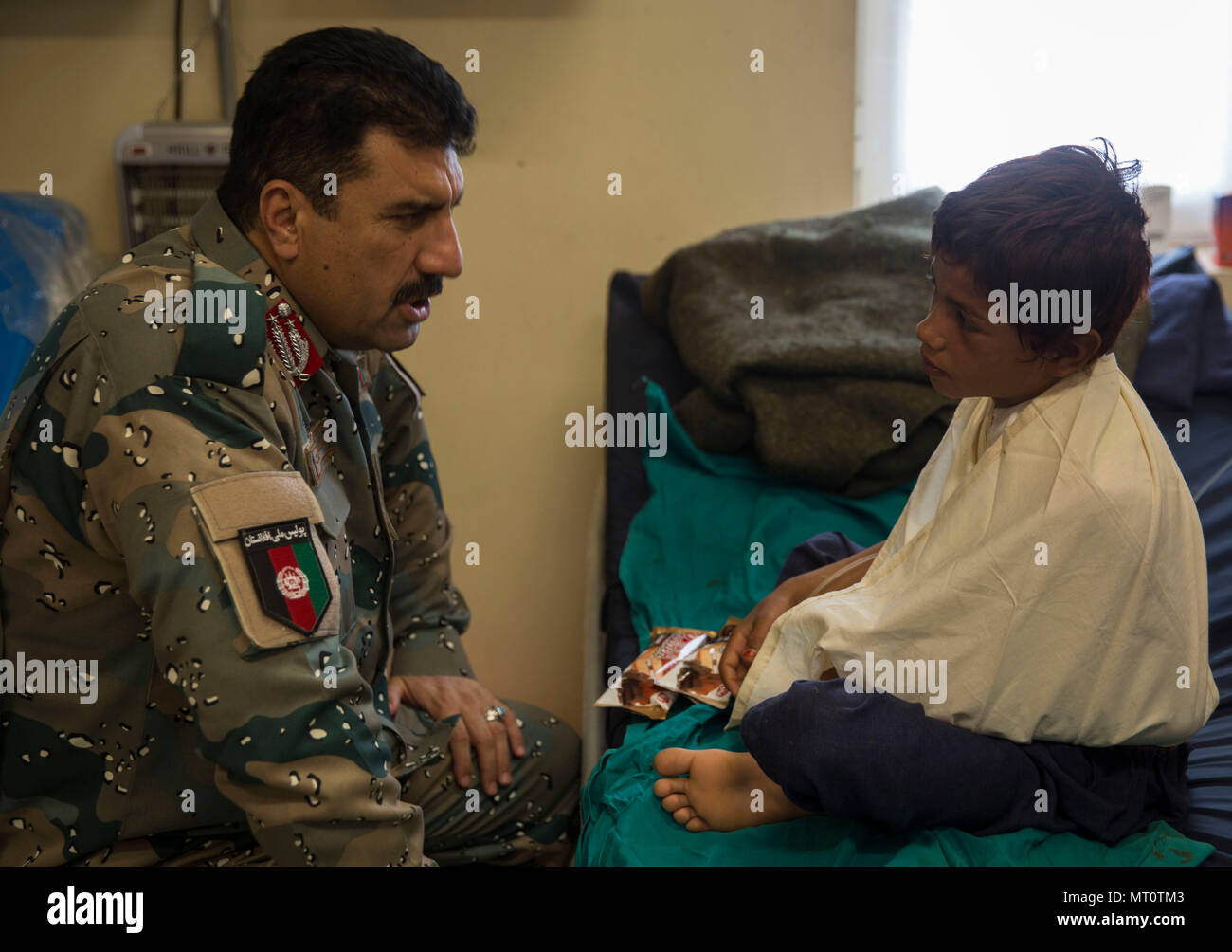 General Daud Ghulam Tarakhel, the commanding general of the 505th Zone National Police, pays a visit to the young boy who was injured during a Taliban rocket attack just outside of Bost Airfield, Afghanistan, July 20, 2017. (U.S. Marine Corps photo by Sgt. Justin T. Updegraff) - Stock Image