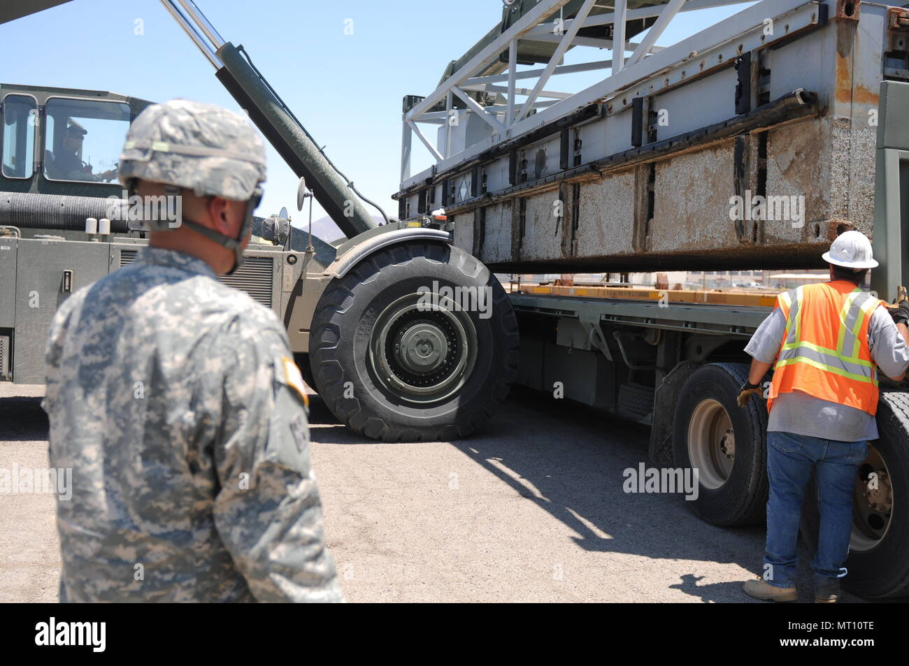 Sgt. Michael Tovar of the 250th Transportation Company out of El Monte, Calif., observes as section a Modular Causeway System (MCS) are loaded onto his M915 truck at the Marine Corps Logistics Base in Yermo, Calif., during Big LOTS West 17. - Stock Image