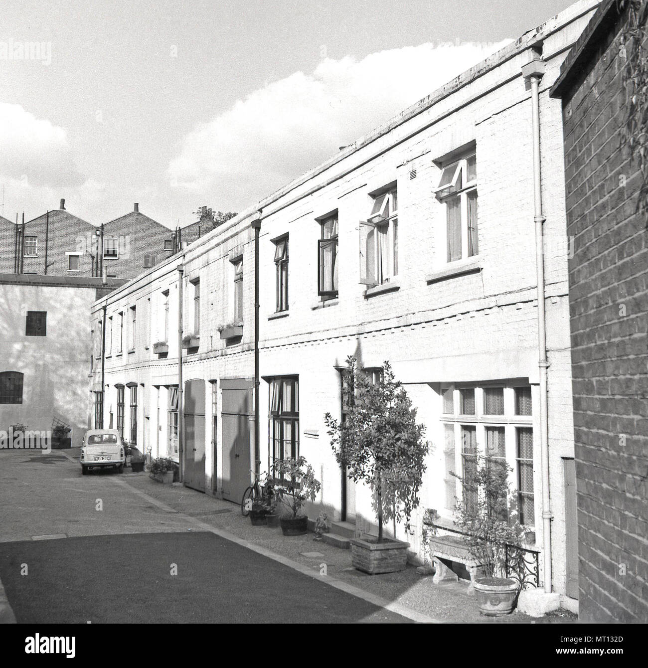1960s, London, a row of small mews houses. These low-rise, two-storey dwellings were converted from former coach houses or stables and built behind larger city houses in service streets. As the name suggests they were originally built for the horse transport of the wealthy city dwellers. The introduction of the motorcar saw the and of the equestrian usage and in this era they became a fashionable place to live, - Stock Image