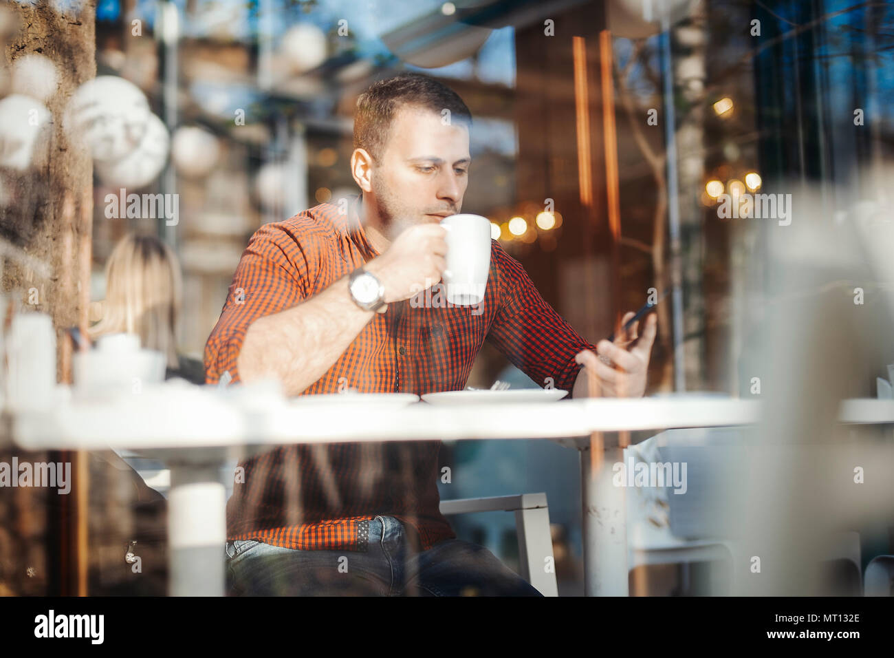 Young attractive man drinking coffee and writing message at mobile phone - Stock Image