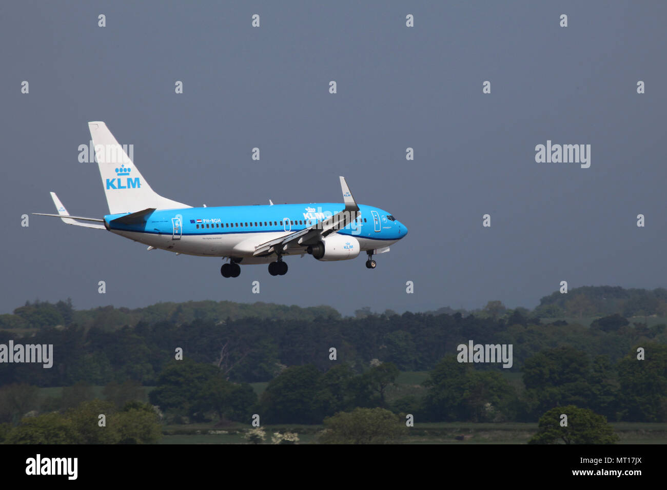 A KLM jet skims the treeline as it makes its final approach into Edinburgh airport - Stock Image