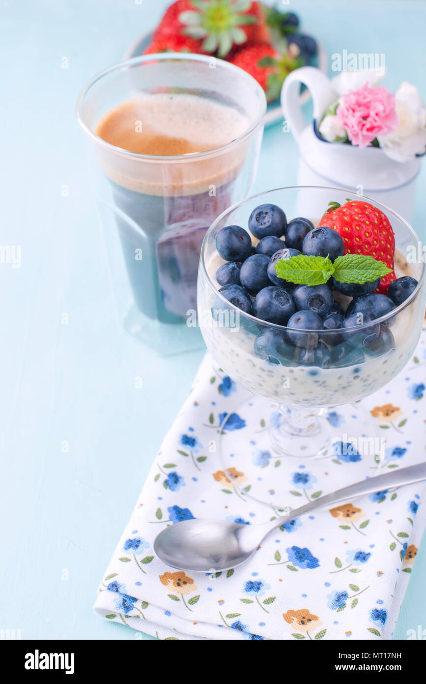 A glass of coffee and pudding chia with blueberries and strawberries for breakfast. Vegetarian healthy food. Blue background. Napkin with flowers and flowers in a vase. Bright colors. - Stock Image