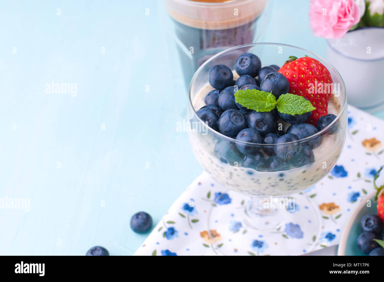 A glass of coffee and pudding chia with blueberries and strawberries for breakfast. Vegetarian food. Blue background. Napkin with flowers. Bright colors. - Stock Image