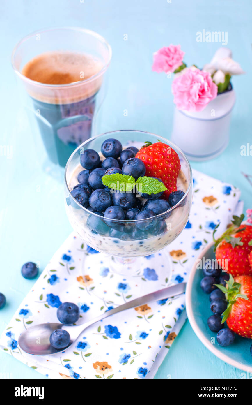 A glass of coffee and pudding chia with blueberries and strawberries for breakfast. Vegetarian food. A small bouquet of flowers and a blue background. Vertical photo. - Stock Image