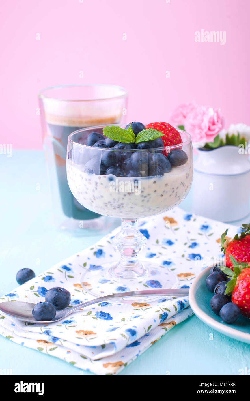 A glass of coffee and pudding chia with blueberries and strawberries for breakfast. Vegetarian food. A small bouquet of flowers and a blue background. Vertical photo - Stock Image
